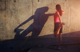 Mujer haciendo deporte con ganas apoyada en una pared
