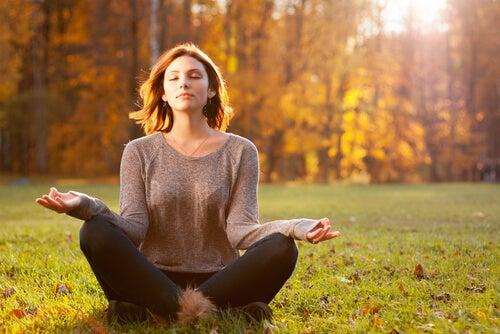 Mujer haciendo meditación en el campo