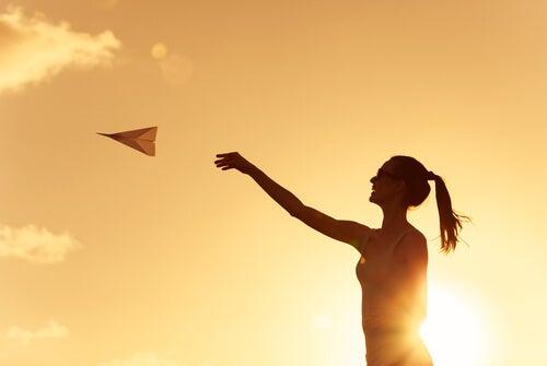 Mujer lanzando un avión de papel