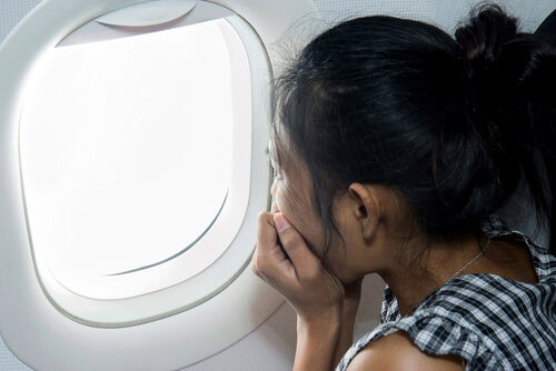 Mujer mirando por la ventanilla del avión con aerofobia