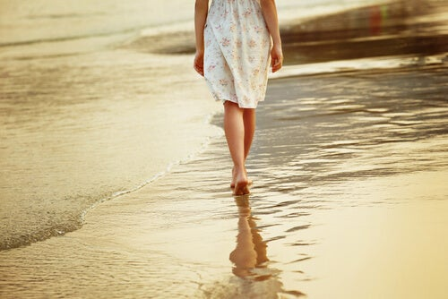 Mujer paseando por la arena de la playa descalza