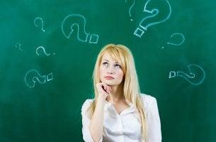 Mujer pensando con interrogaciones dibujadas en una pizarra