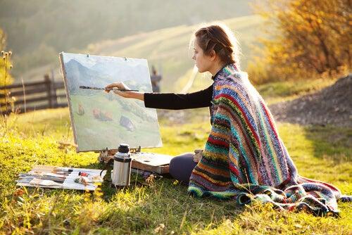 Mujer pintando un cuadro al óleo en el campo