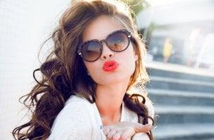 Mujer posando con los labios rojos tirando un beso