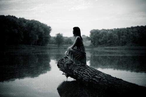 Mujer sentada sobre el río