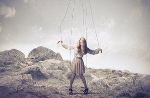 Mujer en forma de marioneta por manipulación emocional invisible