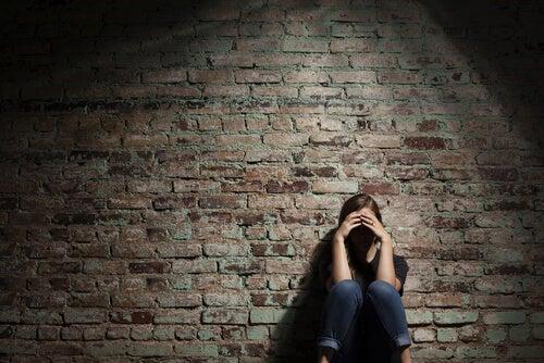 Mujer triste apoyada en la pared