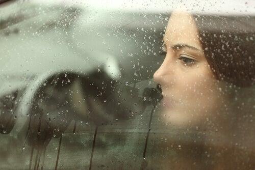 Mujer triste mirando por la ventana de su coche llena de gotas de agua y pensando en ciertos momentos
