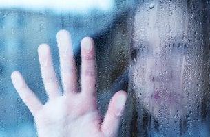 Mujer triste tras un cristal
