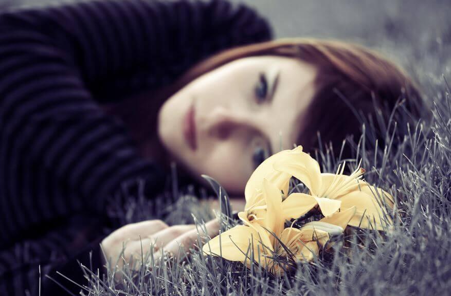 Mujer triste tumbada en el suelo con una flor amarilla