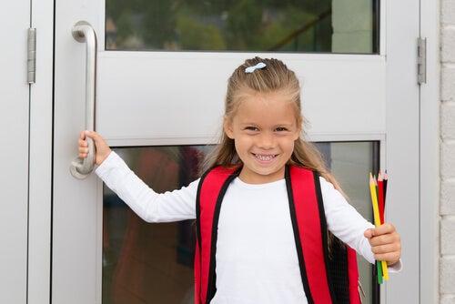 Niña entrando a la puerta del colegio con lápices en la mano