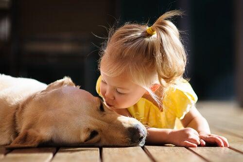Niña tirándole un beso a un perro