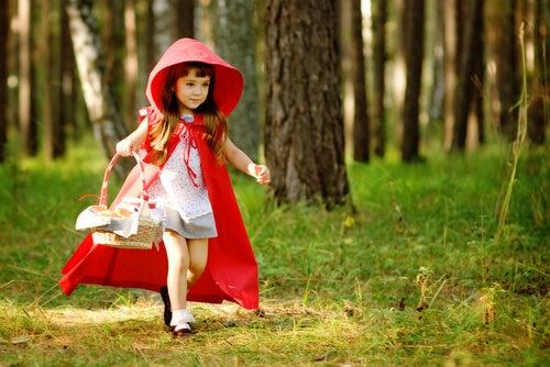 Niña vestida de caperucita roja corriendo