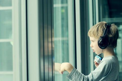 Niño con asperger escuchando música con sus auriculares