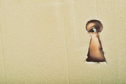Niño con curiosidad mirando por la cerradura de la puerta