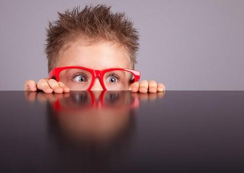 Niño con gafas rojas observando con curiosidad