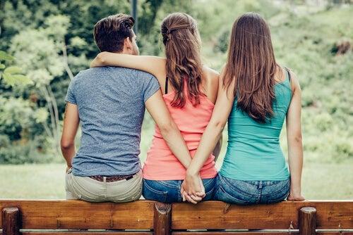Pareja sentada en un banco mientras el chico agarra la mano de su amante