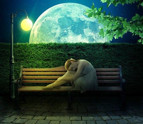 Persona introvertida en un banco a la luz de la luna