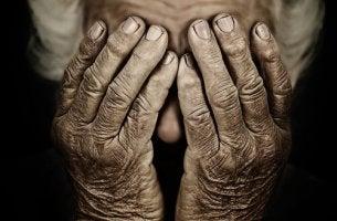 Persona mayor con las manos en la cara preocupada