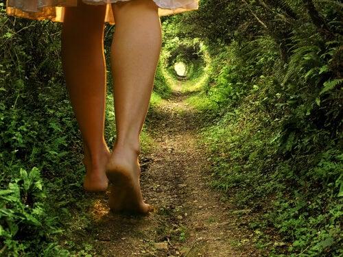 Piernas de una mujer andando hacia una puerta en un jardín