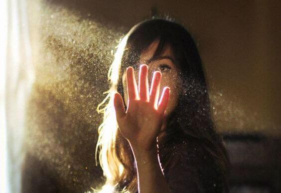 mujer con la mano en un haz de luz