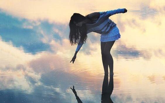 chica tocando su reflejo en el agua