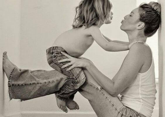 Madre sujetando a su hijo mientras le tira un beso