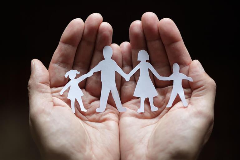 manos con familia de papel