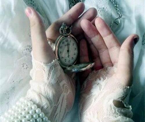 manos con un reloj que marca el presente