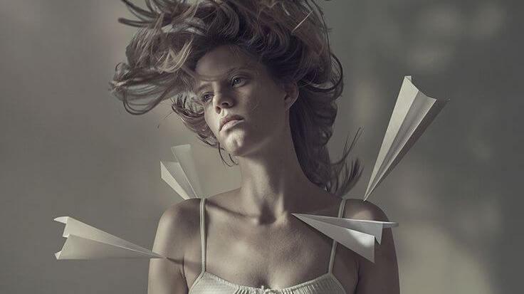 mujer con aviones de papel en el cuerpo