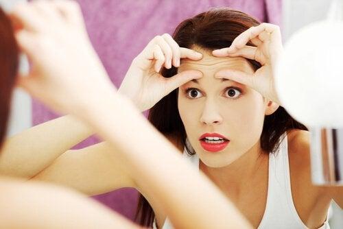 Mujer con miedo a envejecer mirándose a un espejo