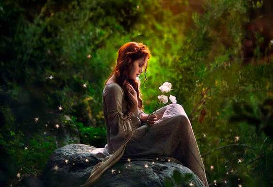 mujer en un bosque sujetando una flor