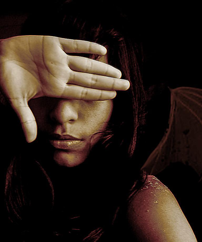 Mujer con mano tapándose los ojos