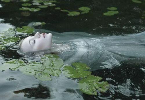 mujer en un río con nenúfares