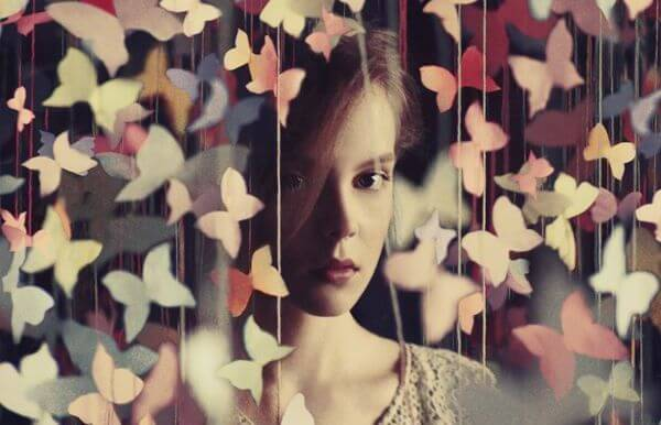 mujer en una cortina formada por mariposas mirando el presente