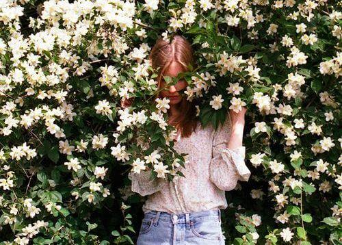 mujer en una enredadera de flores blancas