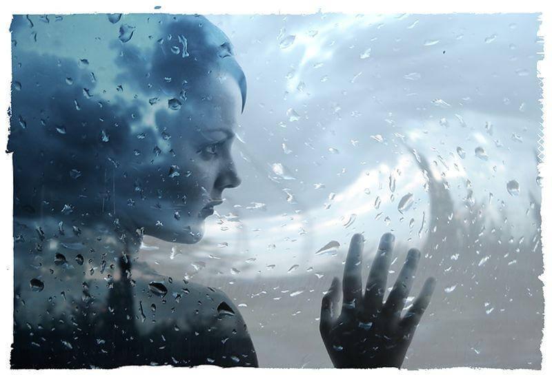 Mujer con depresión mirando por la ventana