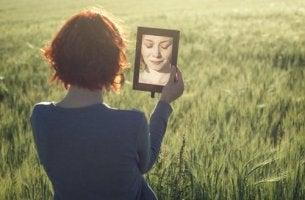 Mujer reflejada en un espejo entre la alegría y la tristeza