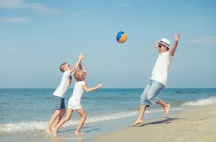 Hombre con hijos jugando en la playa