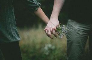 pareja cogida de las manos con ramo de flores