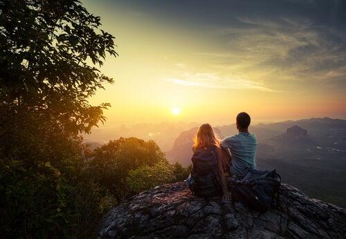 Amigos en la cima de la montaña observando el amanecer
