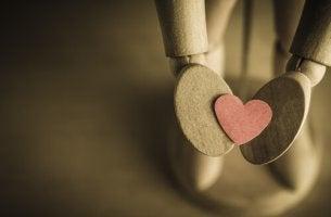Brazos de un muñeco de madera con un corazón