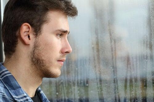 Chico adolescente mirando por la ventana