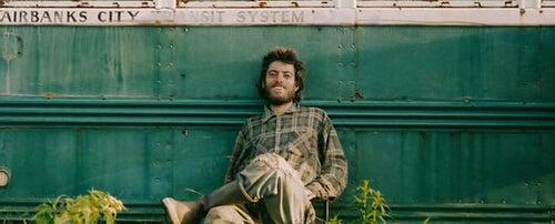 Christopher McCandless sentado apoyado en su caravana