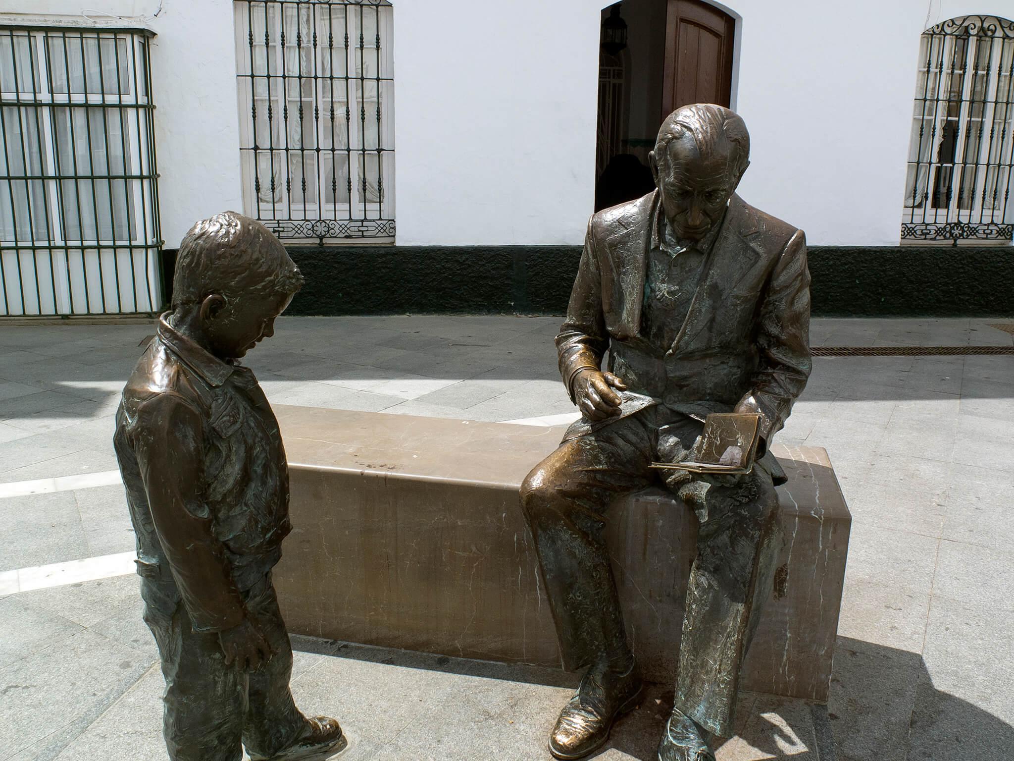 Estatura de José Saramago con un libro y un niño