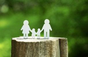 Familia en papel sobre un tronco de árbol