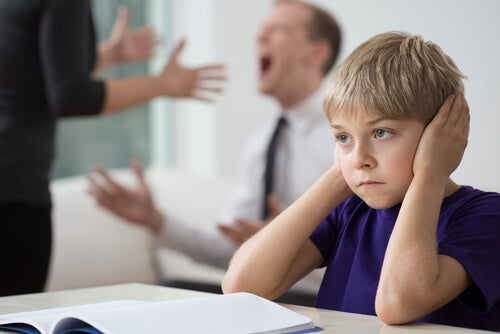 Hijo tapándose los oídos escuchando a sus padres