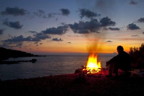 Hombre al anochecer con fuego a la playa