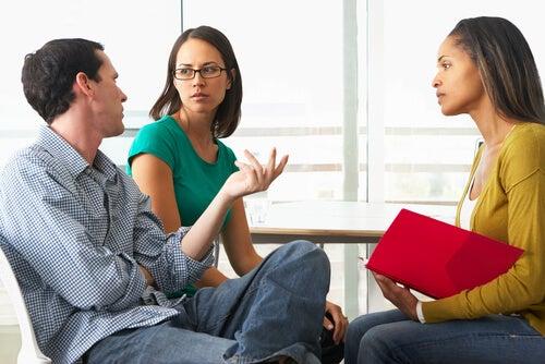 Hombre dando su opinión a sus dos compañeras en una reunión