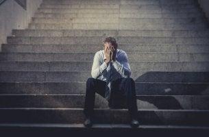 Hombre con las manos en la cara sentado en una escalera afectado por el desempleo